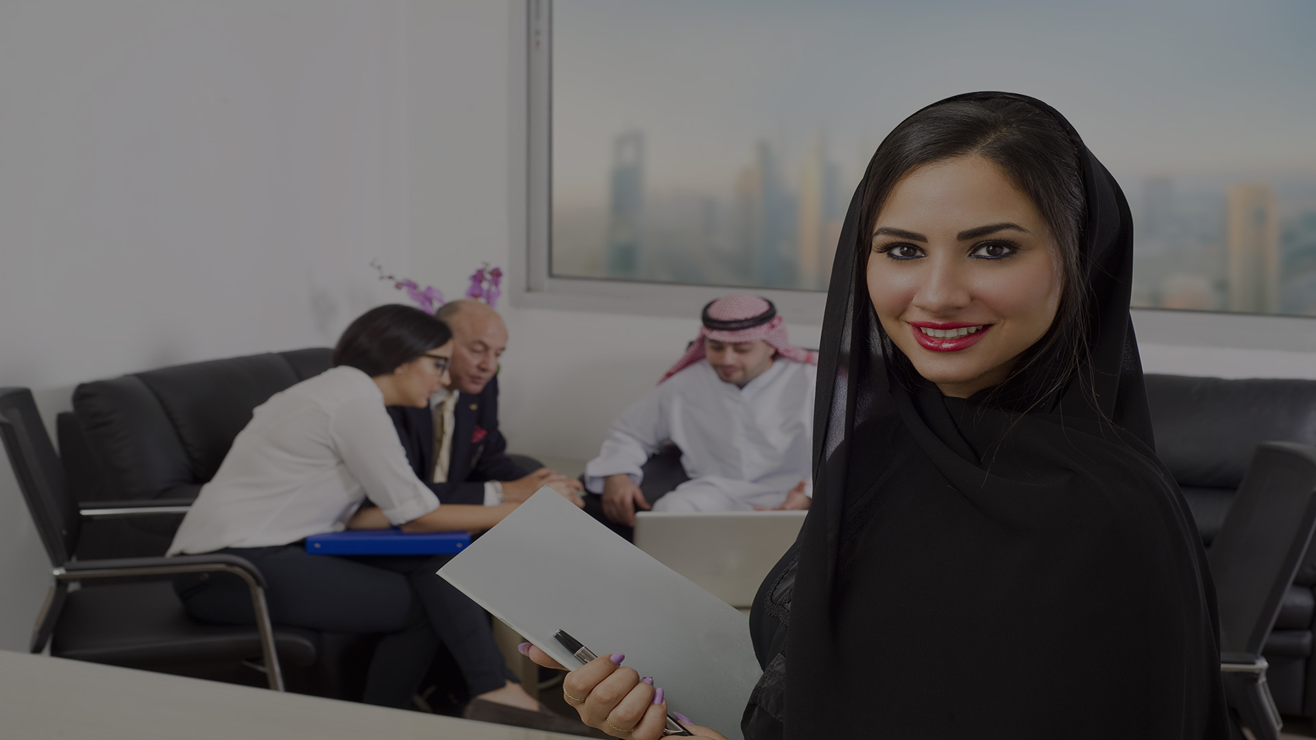 Attractive Muslim woman smiling in offices overlooking Dubai. Colleagues are having a business meeting in the background.